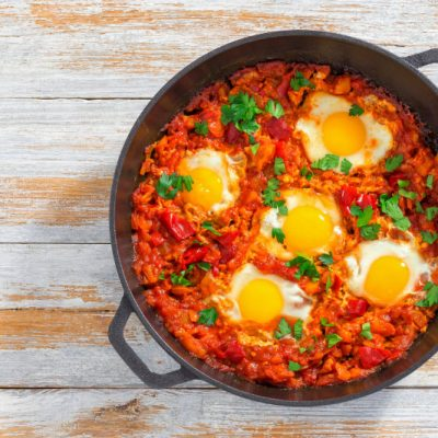 healthy breakfast shakshuka - fried eggs, onion, bell pepper, tomatoes and spices in cast iron stewpan on old wooden background, authentic recipe, view from above