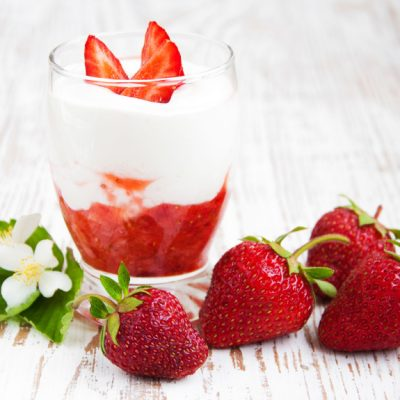 Glass of strawberry yogurt, with fresh strawberries