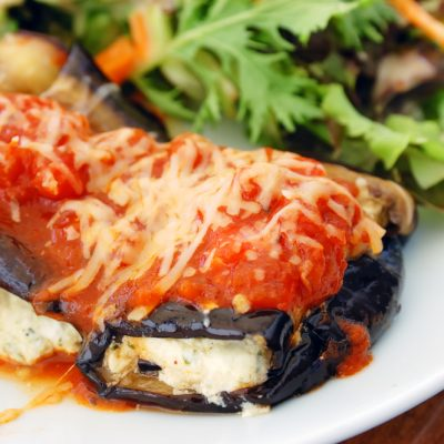 baked eggplant filled with tomato and cheese on a plate